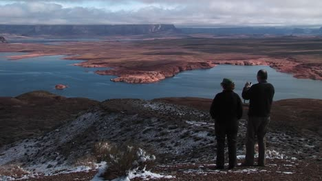 Mediumshot-Of-A-Couple-Standing-On-A-Snowdusted-Area-Looking-Over-Lake-Powell-Arizona