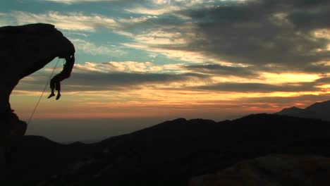 Panleft-Of-A-Silhouetted-Rockclimber-Hanging-From-An-Overhanging-Rock-Face-With-California-Sunset-Beyond