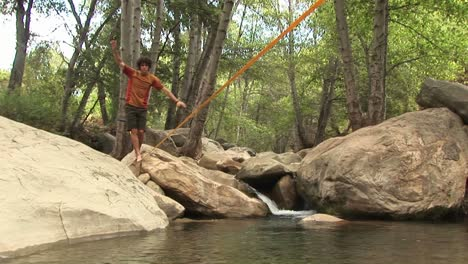 Mediumshot-Of-A-Young-Man-Slacklining-Across-A-Swimming-Hole