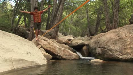Jibup-Of-A-Young-Man-Slacklining-Across-A-Placid-Swimming-Hole