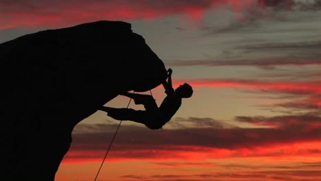 Mediumshot-Of-A-Silhouetted-Climber-Hanging-From-An-Overhang-Rock-Face-With-A-Beautiful-California-Sunset-In-The-Distance