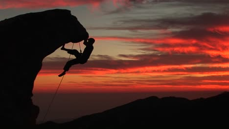 A-Man-Climbs-A-Rugged-Peak-In-Silhouette-At-Sunset