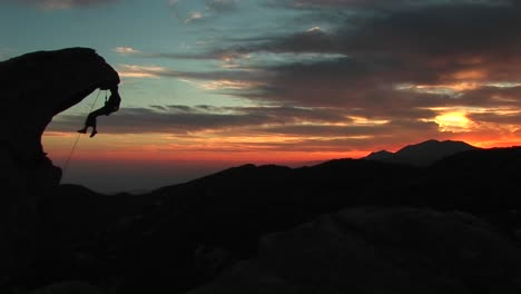 Mediumshot-Of-A-Rockclimber-Silhouetted-By-The-Settingsun-Hanging-From-An-Rock-Overhang
