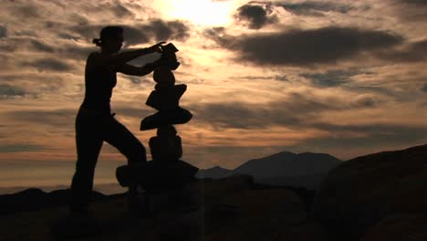 Mediumshot-Of-A-Silhouetted-Woman-Stacking-Rocks-On-A-Mountaintop