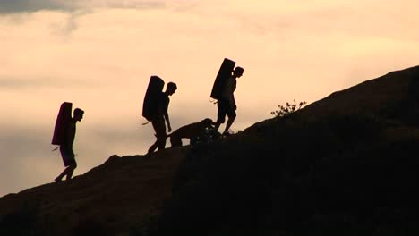 Mediumshot-Of-A-Group-Of-Silhouetted-Backpackers-And-A-Dog-Climbing-A-Rock-Structure