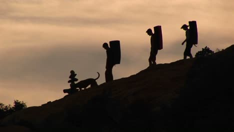 Panleft-Of-Three-Backpackers-And-A-Dog-Silhouetted-Against-An-Evening-Sky
