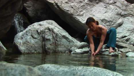 Medium-Shot-Of-A-Woman-Rockclimber-Washing-Her-Hands-In-A-Mountain-Pool