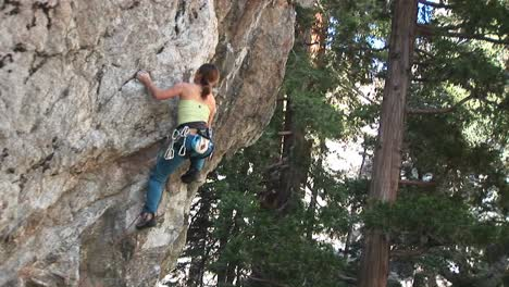Mediumshot-Of-A-Rock-Climber-Making-Her-Way-Up-A-Sheer-Granite-Cliff-Face