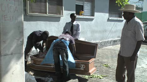 A-victim-of-the-Haiti-earthquake-is-loaded-into-a-coffin