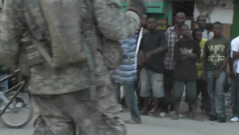 Victims-hold-up-an-American-flag-while-armed-soldier-guards-relief-efforts-in-haiti