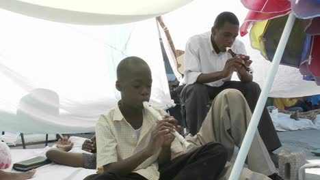 Men-in-a-refugee-center-play-flutes-following-the-Haiti-earthquake