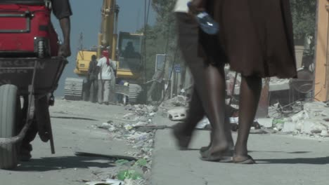 People-walk-amongst-the-rubble-following-a-devastating-earthquake-in-Haiti