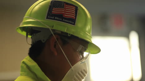 An-American-factory-worker-wears-a-helmet-with-a-flag