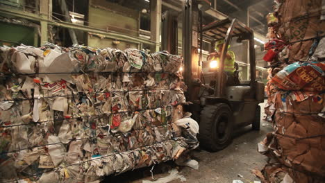 A-skip-loader-moves-pallets-of-recycled-materials-in-a-factory
