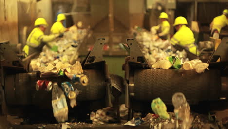Excellent-shot-of-workers-in-a-recycling-center-sorting-trash-on-conveyor-belts