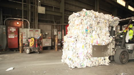 Step-motion-of-a-skip-loader-moves-aluminum-cans-at-a-recycling-center