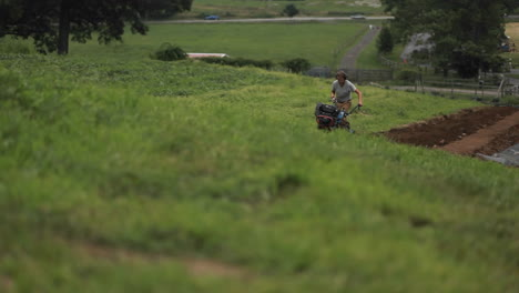 A-man-pushes-a-piece-of-farm-equipment-in-an-agricultural-field-2