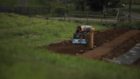 A-man-pushes-a-piece-of-farm-equipment-in-an-agricultural-field-3