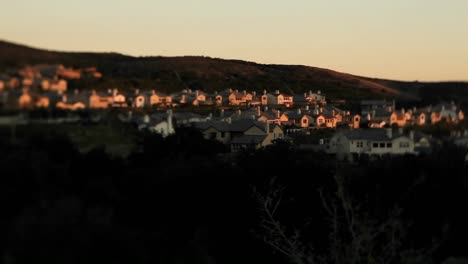 Tract-homes-behind-a-for-sale-in-an-upscale-urban-neighborhood-at-dusk