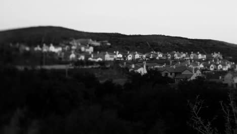 Black-and-white-shot-of-tract-homes-behind-a-for-sale-in-an-upscale-urban-neighborhood-at-dusk