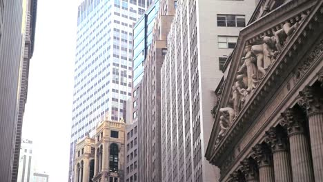 Low-angle-pan-right-view-of-skyscrapers-lining-Wall-Street-in-New-York-City