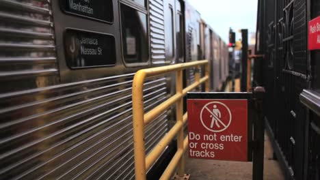 A-train-pulls-out-of-a-station-in-New-York-City-next-to-a-sign-warning-travellers-to-not-enter-or-cross-the-tracks