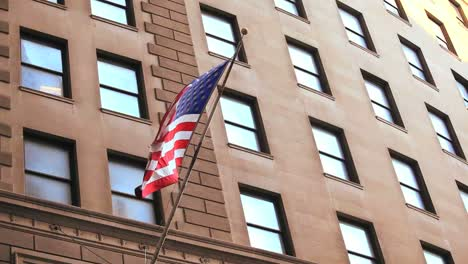 The-American-flag-waves-from-a-building-on-Wall-Street-in-New-York-City