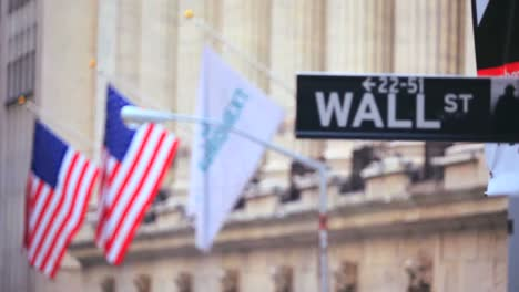 Pull-focus-shot-between-American-flags-and-a-sign-reading-Wall-St-in-New-York-City