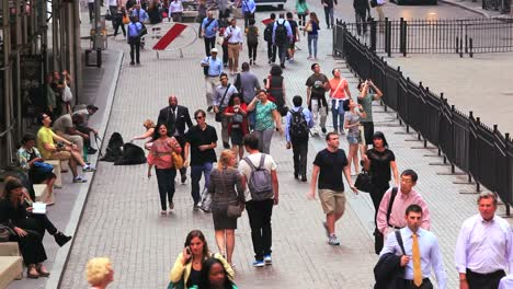 High-angle-shot-of-pedestrians-walking-along-Wall-Street-in-New-York-City