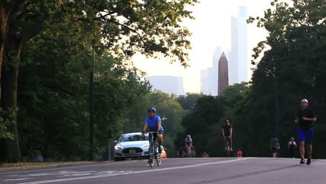 Joggers-and-bicyclists-pass-along-a-path-in-Central-Park-in-New-York-City