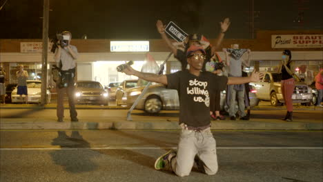 Protestors-fall-to-their-knees-to-oncoming-police-in-the-Ferguson-riots