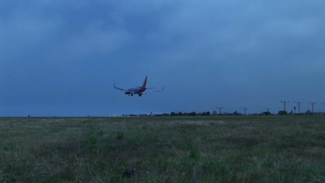 A-jet-airplane-lands-on-an-airport-runway-against-darkened-skies