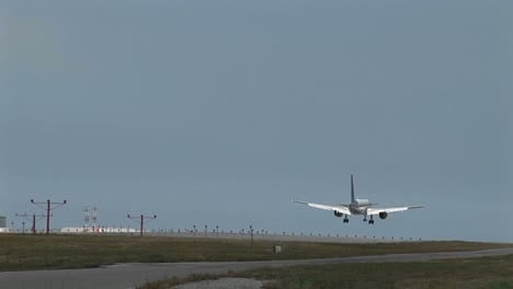 Wide-shot-of-jet-airplane-lands-on-an-airport-runway