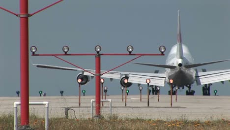 A-747-jet-lands-on-an-airport-runway-behind-lights-and-guide-beacons