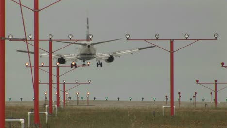 An-airplane-landing-on-a-runway-through-lights-and-guidance-equipment-beams