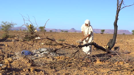 An-old-Moroccan-man-chops-wood-in-the-desert