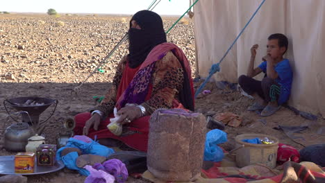 A-Muslim-woman-and-her-children-sit-outside-their-tent-in-the-desert-of-Morocco