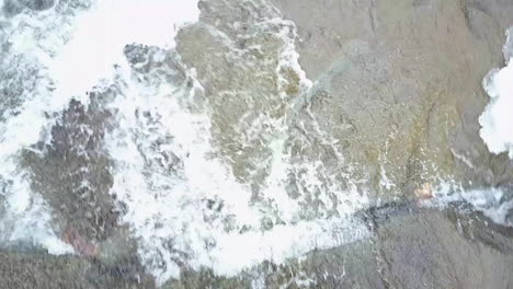Beautiful-POV-aerial-looking-straight-down-of-a-river-flowing-in-a-frozen-landscape