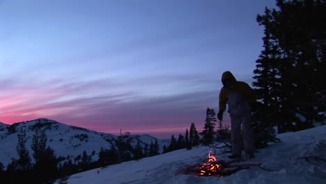 Panning-shot-from-snowy-mountains-to-a-hiker-tending-a-campfire