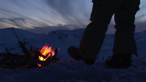 Closeup-of-a-man-s-legs-beside-a-campfire-in-winter