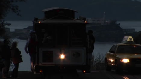 Mediumshot-of-a-San-Francisco-cable-car-with-Alcatraz-Island-in-the-distance