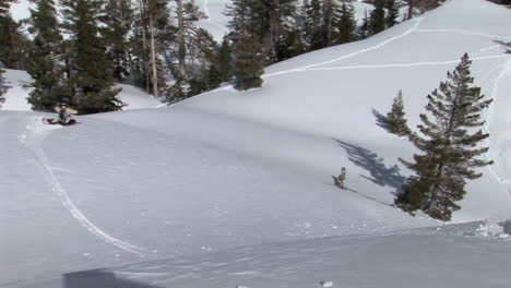 Medium-shot-of-a-snowboarder-passing-and-leaving-powder-on-the-lens-of-the-camera