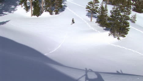 Following-shot-of-a-snowboarder-as-he-makes-a-thrilling-jump-from-a-cliff-and-makes-a-good-landing