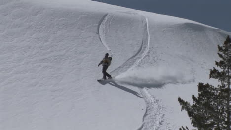 Following-shot-of-a-snowboarder-as-he-boards-slowly-down-a-slope-of-virgin-powder