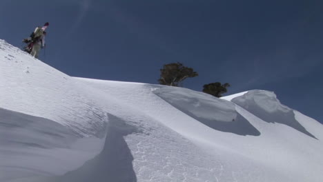 Longshot-of-hikers-ascending-a-snowy-mountain-with-snowboards-on-their-backs