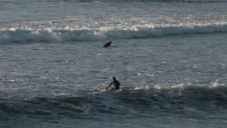 A-surfer-paddles-out-on-his-board-into-the-waves-along-the-coast-of-California