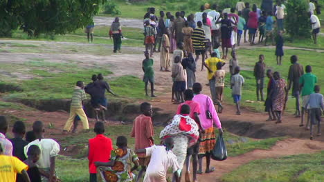 Longshot-of-African-niños-run-down-a-country-road