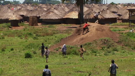 Longshot-of-young-niños-run-and-playing-in-a-village-or-refugee-camp-in-Northern-Uganda