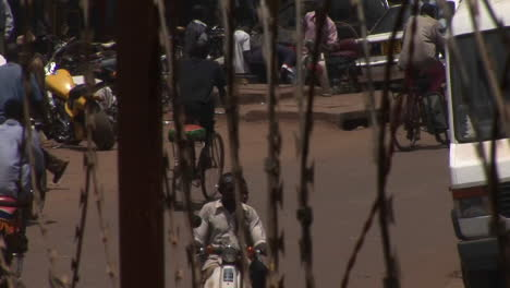 Bicycles-and-motorcycles-drive-behind-a-barbed-wire-fence-in-Uganda