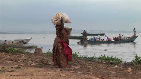 Panright-of-a-heavily-laden-woman-carrying-parcels-to-a-fishing-boat-on-the-shores-of-Lake-Victoria